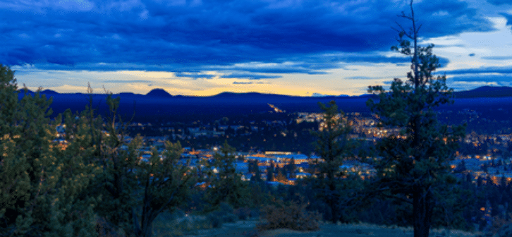 View looking down at Bend Oregon at dusk. Lights are on in buildings and clouds are in the sky.