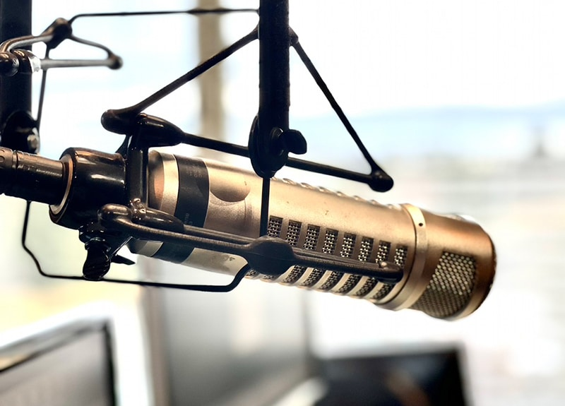 A closeup image of a silver microphone used to record the podcast